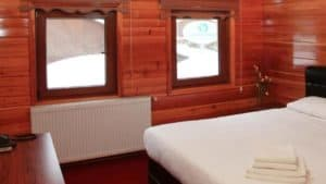 كوخ خشبي ريفي مع نوافذ وسرير