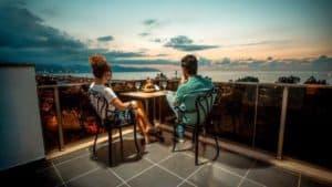 شخصين جالسين على تراس مطل على السماء والبحر