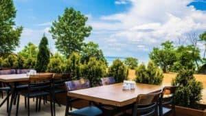 طاولات وكراسي في حديقة مطلة على البحر
