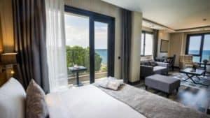 غرفة بسرير مزدوج مع كنبة وشرفة على البحر