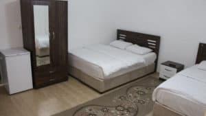 غرفة مع سرير مزدوج وسرير مفرد ودولاب