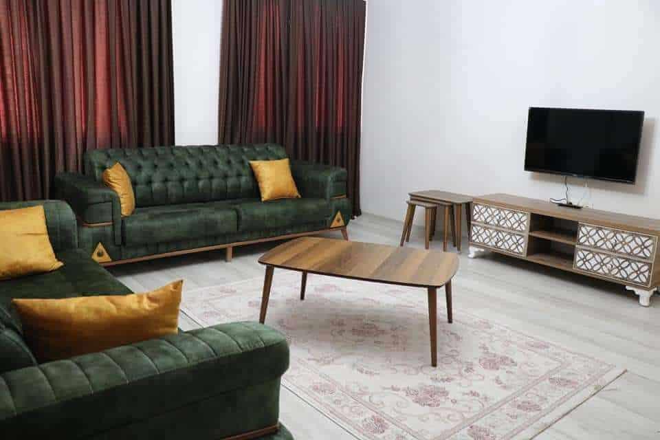 غرفة جلوس مع كنبات وتلفزيون وستائر