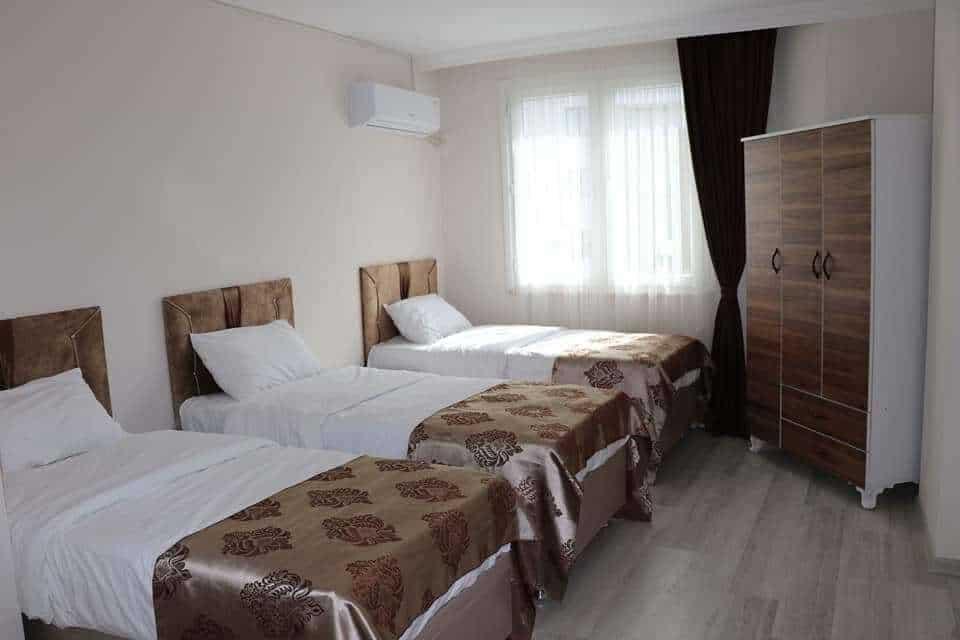 غرفة مع 3 اسرة وتكييف وستائر
