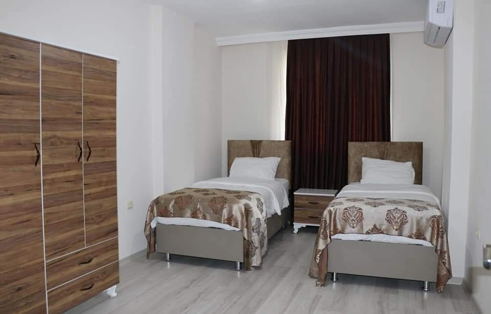 غرفة مع سريرين مفردين ودولاتب وستائر