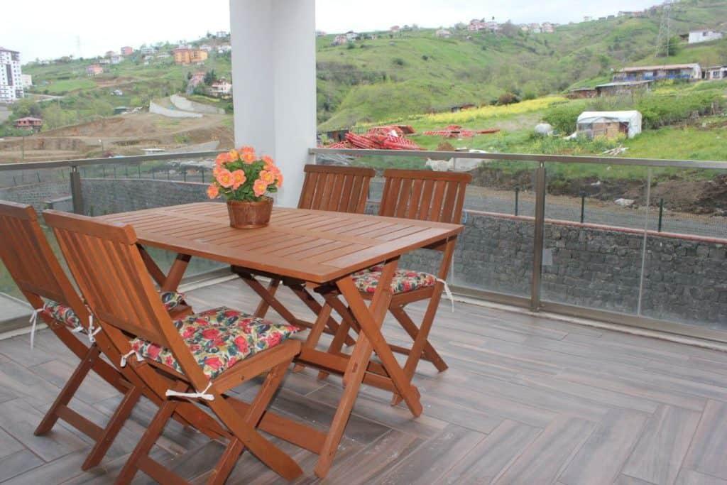 شرفة مع طاولة وكراسي خشبية مطلة على الطبية
