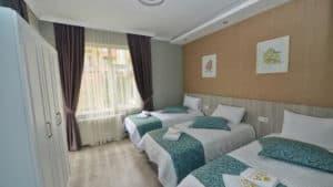 غرفة بثلاث اسرة مع خزانة وستائر