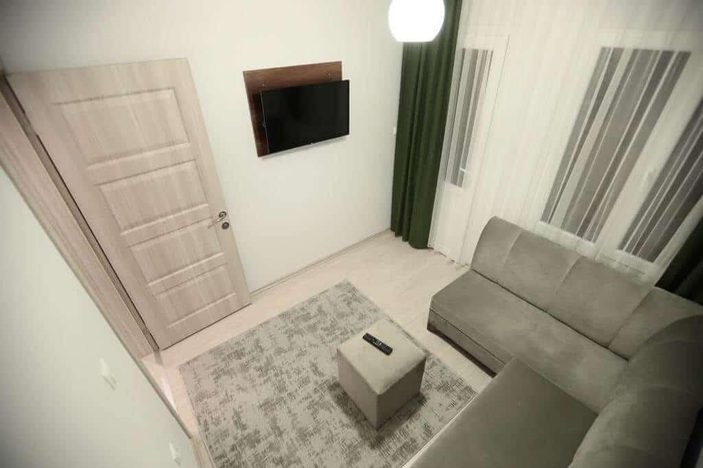 غرفة جلوس مع شاشة وستائر