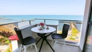 كرسيين مع طاولة صغيرة على شرفة مطلة على البحر